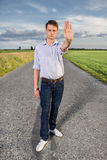 Full length portrait of senior young man showing stop gesture on country road Royalty Free Stock Images