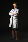 Full length portrait of serious doctor woman on black background. In white robe royalty free stock images