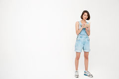 Full length portrait of serious pretty girl, making notes. Full length portrait of serious pretty girl, in gray shirt and denim overall, making notes, isolated Royalty Free Stock Image