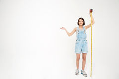 Full length portrait of a seriously pretty girl, holding measure Royalty Free Stock Image