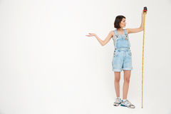 Full length portrait of a seriously pretty girl, holding measure Royalty Free Stock Images