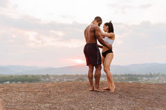 Full-length portrait of sexy fit mixed race couple with perfect bodies in sportswear softly embracing on mountains Royalty Free Stock Images