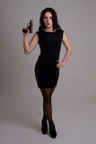 Full length portrait of sexy woman in black dress with gun over Stock Photos