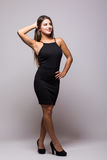 Full length portrait of a sexy woman in little black fashion dress on grey Stock Images