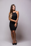 Full length portrait of a sexy woman in little black fashion dress on grey Stock Photography
