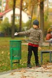 Full length portrait of a six year old boy throwing paper to the trash bin / garbage can in the park. Full length portrait of a six year old boy throwing paper royalty free stock photo