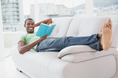 Full length portrait of smiling Afro man reading a book on sofa Stock Photography