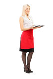 Full length portrait of a smiling blond female waitress holding Stock Image