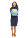 Full length portrait of smiling business woman showing globe. Isolated on white stock photography