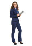Full length portrait of smiling business woman with tablet pc Royalty Free Stock Images