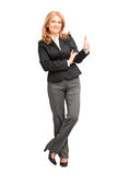 Full length portrait of a smiling businesswoman leaning on wall Stock Image