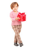 Full length portrait of a smiling child holding a gift. Against white background Royalty Free Stock Image