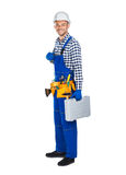 Full length portrait of smiling construction worker in uniform w. Ith toolbox isolated on white background Royalty Free Stock Images