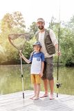 Full length portrait of smiling father and son standing with fishing tackles on pier against lake stock photos