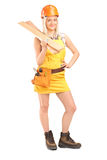 Full length portrait of a smiling female carpenter with helmet h Royalty Free Stock Photo