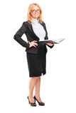 Full length portrait of a smiling female teacher holding a noteb Stock Image