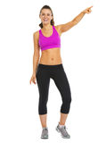 Full length portrait of smiling fitness young woman pointing on Royalty Free Stock Photo