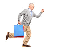 Full length portrait of a smiling gentleman running with shoppin Stock Photos