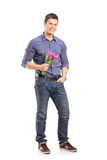 Full length portrait of a smiling guy holding flowers and lookin Royalty Free Stock Image