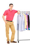 Full length portrait of a smiling guy posing on a hang rail full. Of clothes isolated on white background Royalty Free Stock Images