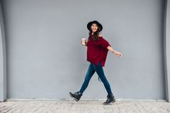 Full length portrait of a smiling joyful asian girl. Dressed in hat and sweater holding coffee cup while walking on a city street royalty free stock image