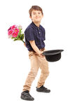 Full length portrait of a smiling kid holding bunch of flowers a. Nd hat isolated on white background Stock Image