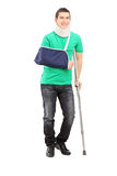 Full length portrait of a smiling male with broken arm and crutc Royalty Free Stock Image