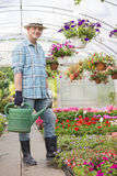 Full-length portrait of smiling man carrying watering can in greenhouse Royalty Free Stock Photo