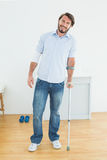 Full length portrait of a smiling man with crutch Royalty Free Stock Images