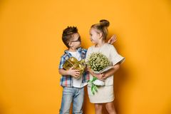 Full length portrait of a smiling man giving a present box to his girlfriend over gray wall. Picture of happy young couple boy and girl standing over yellow wall stock images