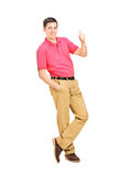 Full length portrait of a smiling man leaning against wall and g Stock Photography