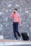 Full length smiling man talking on smart phone with luggage Royalty Free Stock Images