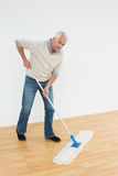 Full length portrait of a smiling mature man mopping the floor Stock Image
