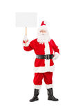 Full length portrait of a smiling Santa Claus holding a panel Stock Photos