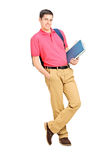 Full length portrait of a smiling student holding books and lean Stock Photos