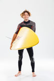 Full length portrait of a smiling surfer holding surf board Royalty Free Stock Photography