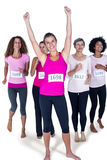 Full length portrait of smiling winner athlete with arms raised and others running Stock Photography