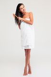 Full length portrait of a smiling woman combing her hair Royalty Free Stock Images
