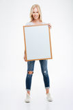 Full length portrait of a smiling woman holding blank board. Isolated on a white background Royalty Free Stock Image