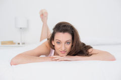 Full length portrait of a smiling woman resting in bed Royalty Free Stock Image