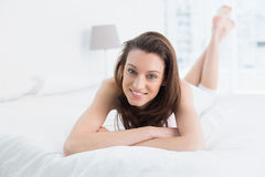 Full length portrait of a smiling woman resting in bed Royalty Free Stock Images