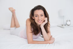 Full length portrait of smiling woman resting in bed Stock Photography
