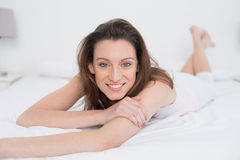 Full length portrait of smiling woman resting in bed Royalty Free Stock Image
