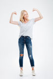 Full length portrait of a smiling woman showing her muscles Royalty Free Stock Photo