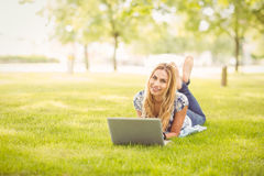 Full length portrait of smiling woman using laptop at park Stock Photography