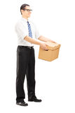 Full length portrait of a smiling young man giving a box to some Royalty Free Stock Image