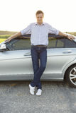 Full length portrait of smiling young man leaning on car at countryside Royalty Free Stock Photo