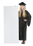 Girl in graduation gown showing blank billboard Stock Photo