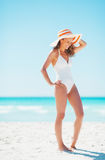 Full length portrait of smiling young woman in hat on beach Royalty Free Stock Photo