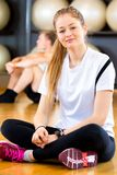 Smiling Woman Sitting Cross Legged In Fitness Center. Full length portrait of smiling young woman sitting cross legged in fitness center Stock Photography